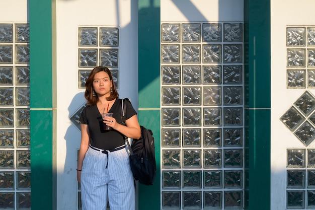 Retrato de uma jovem bela turista asiática carregando uma mochila na estação ferroviária