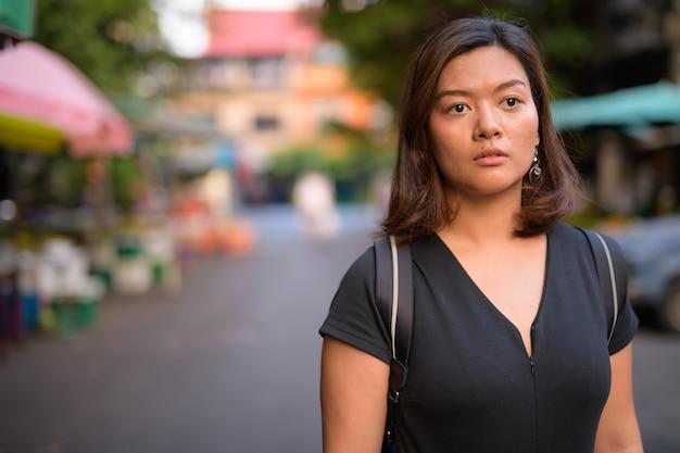 Retrato de uma jovem bela turista asiática explorando as ruas de bangkok