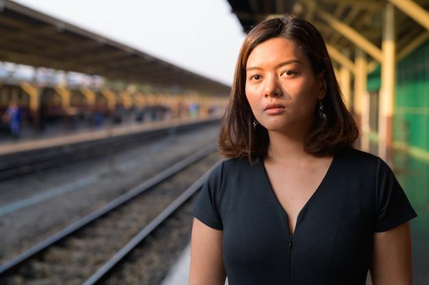 Retrato de uma jovem bela turista asiática na estação ferroviária hua lamphong em bangkok Foto Premium