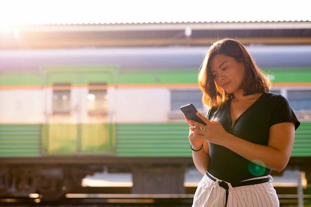 Retrato de uma jovem bela turista asiática na estação ferroviária hua lamphong em bangkok
