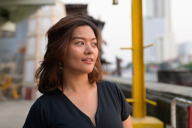 Retrato de uma jovem bela turista asiática no cais à beira do rio Foto Premium