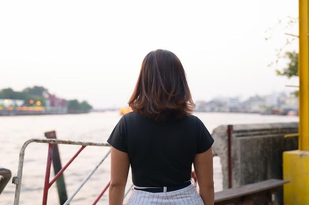 Retrato de uma jovem bela turista asiática no cais à beira do rio
