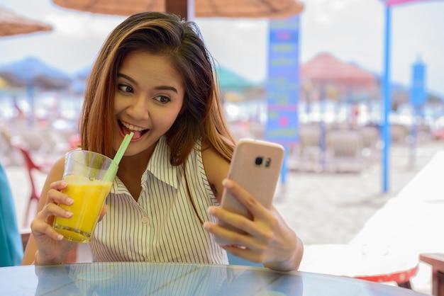 Retrato de uma jovem bela turista asiática sentada em um restaurante na praia ao ar livre