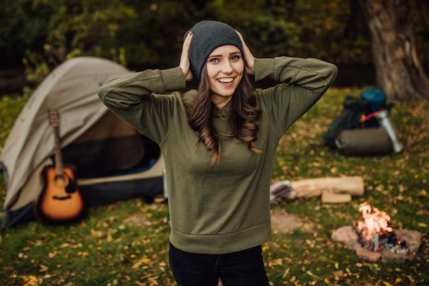 Retrato de uma jovem bela turista feminina na floresta perto da barraca e do saco de dormir