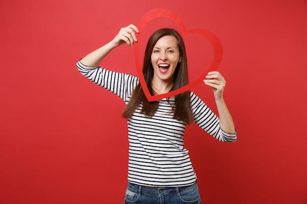 Retrato de uma jovem bonita alegre em roupas listradas casuais, segurando um grande coração de madeira vermelho isolado no fundo da parede vermelha brilhante. emoções sinceras de pessoas, conceito de estilo de vida. simule o espaço da cópia.
