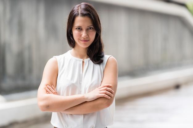 Retrato de uma jovem bonita ao ar livre com os braços cruzados