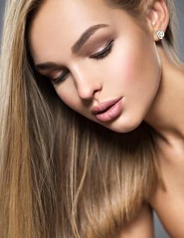 Retrato de uma jovem bonita com cabelos lisos longos claros e maquiagem marrom. garota linda linda posando