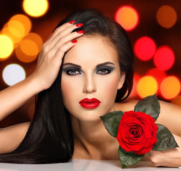 Retrato de uma jovem bonita com lábios vermelhos, unhas e flor rosa na mão. modelo com maquiagem nos olhos roxos, posando no estúdio durante as bolas de luzes à noite. conceito de fundo de bokeh suave.