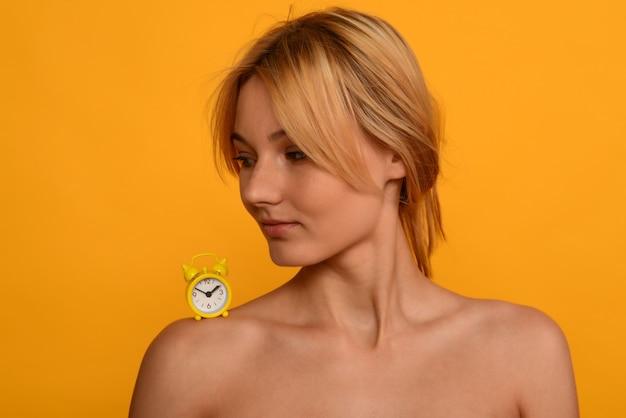 Retrato de uma jovem bonita com o relógio no ombro. o conceito de envelhecimento. tempo e juventude não são eternos