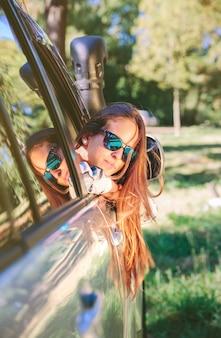 Retrato de uma jovem bonita com óculos escuros e cabelo comprido, olhando para trás pela janela do carro, sobre um fundo de natureza