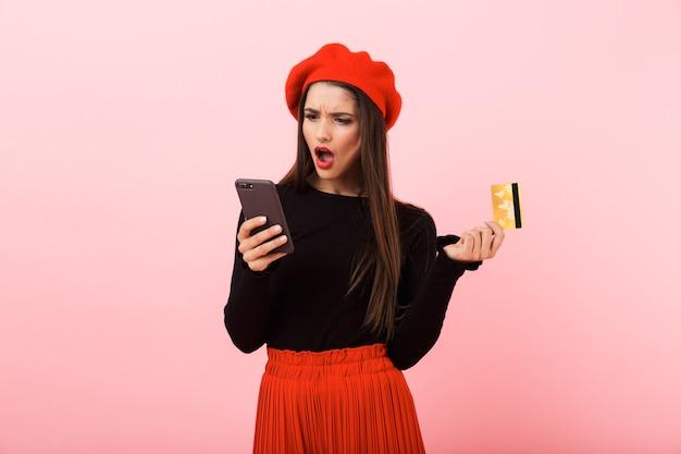 Retrato de uma jovem bonita com raiva, usando uma boina vermelha em pé, isolado sobre um fundo rosa, olhando para o celular, segurando um cartão de crédito de plástico