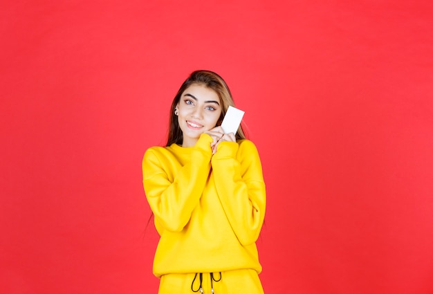 Retrato de uma jovem bonita com um cartão de visita em branco em pé e posando