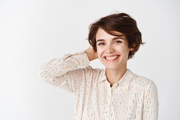 Retrato de uma jovem bonita com um sorriso branco, em pé com uma blusa e tocando o cabelo curto, em pé sobre uma parede branca
