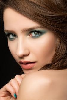Retrato de uma jovem bonita com unhas azuis e maquiagem nos olhos, olhando por cima do ombro