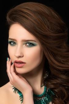 Retrato de uma jovem bonita com unhas azuis e maquiagem nos olhos tocando seu rosto
