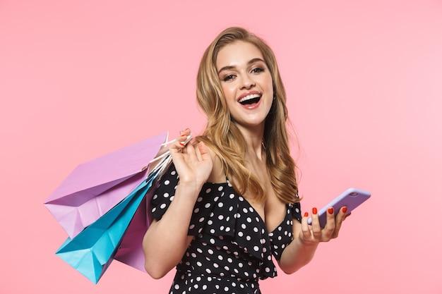Retrato de uma jovem bonita com vestido de pé isolado na parede rosa, carregando sacolas de compras, usando telefone celular