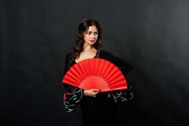 Retrato de uma jovem bonita dançando flamenco com ventilador no estúdio