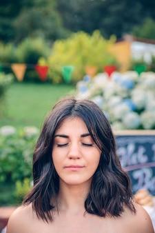 Retrato de uma jovem bonita de cabelo preto com os olhos fechados contra o jardim em uma festa de verão ao ar livre