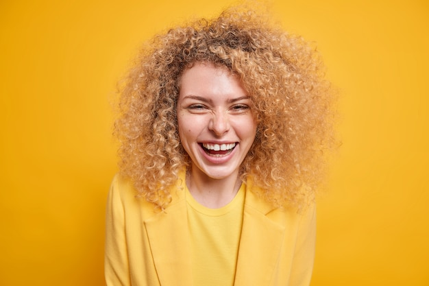 Retrato de uma jovem bonita de cabelos cacheados com um sorriso que expressa amplamente emoções positivas, feliz por saber das notícias recentes