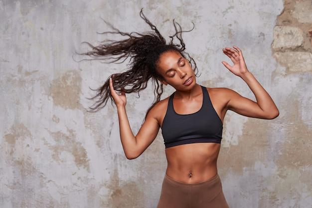 Retrato de uma jovem bonita de pele escura balançando seus longos cabelos castanhos encaracolados enquanto posava sobre o interior do loft, levantando as mãos e mantendo os olhos fechados, vestida com roupas esportivas