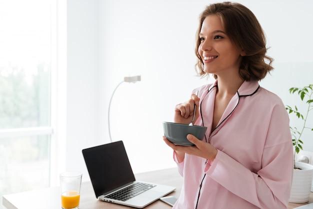 Retrato de uma jovem bonita de pijama, tomando um café da manhã
