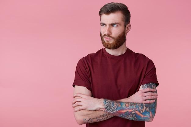 Retrato de uma jovem bonita descontente com barba ruiva e mão tatuada, de mãos cruzadas, carranca e desviar o olhar isolado sobre fundo rosa. conceito de pessoas e emoção.