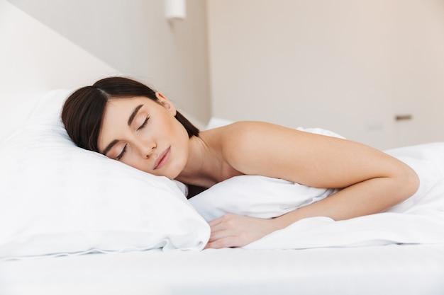 Retrato de uma jovem bonita dormindo na cama