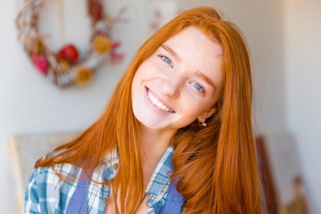 Retrato de uma jovem bonita e feliz com longos cabelos vermelhos olhando para a câmera e sorrindo