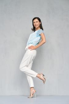 Retrato de uma jovem bonita e feliz na blusa de cetim azul, calça jeans branca e estiletes prata no perfil