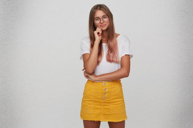 Retrato de uma jovem bonita e feliz usa camiseta, saia amarela e óculos em pé e mantém as mãos postas isoladas sobre a parede branca