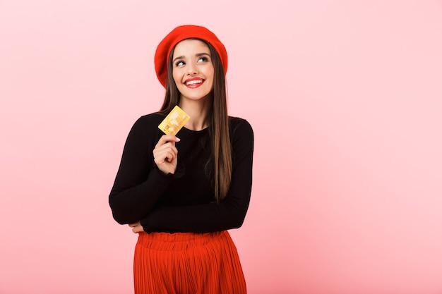 Retrato de uma jovem bonita e feliz, usando uma boina vermelha em pé, isolado sobre um fundo rosa, segurando um cartão de crédito de plástico