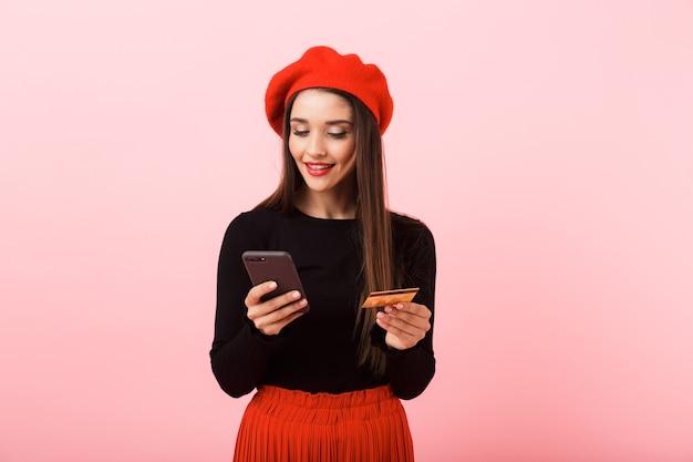 Retrato de uma jovem bonita e feliz, usando uma boina vermelha em pé, isolado sobre um fundo rosa, segurando um telefone celular e um cartão de crédito de plástico
