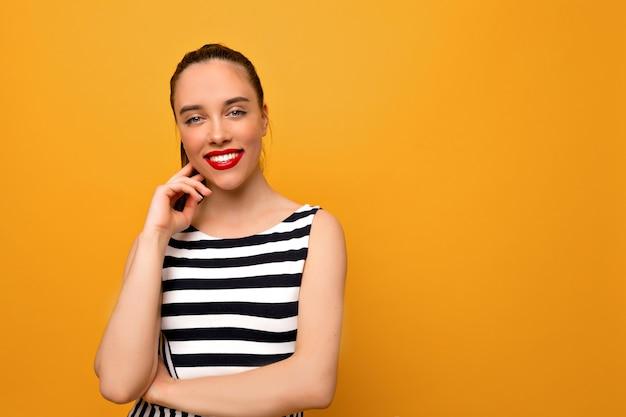 Retrato de uma jovem bonita e sensível vestida de camiseta branca e preta posa com um sorriso encantador sobre a parede amarela, ela cruza os braços, sorri e olha diretamente