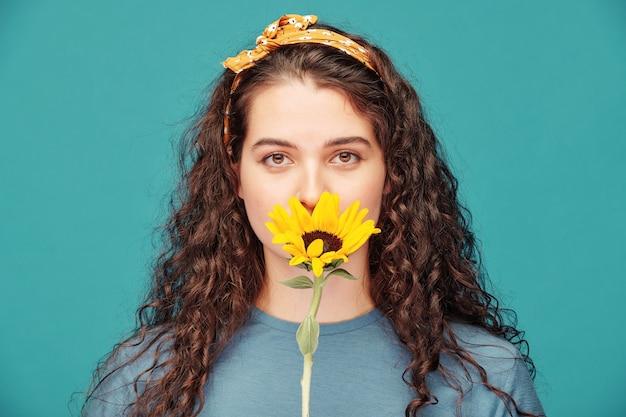 Retrato de uma jovem bonita e serena com cabelo encaracolado cheirando a flor amarela sobre azul