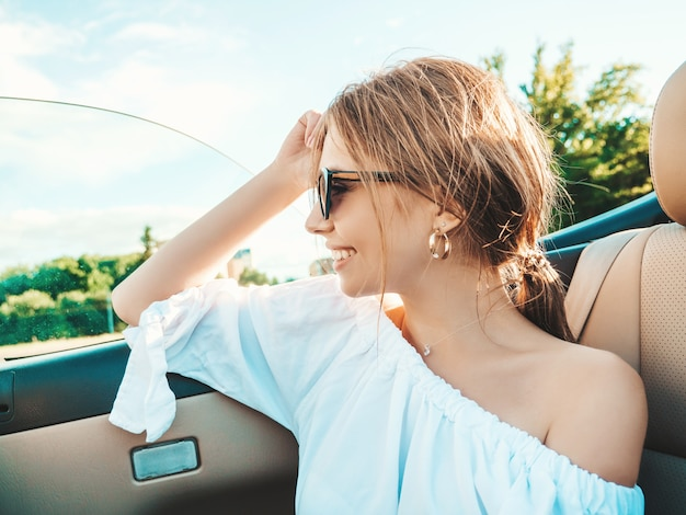Retrato de uma jovem bonita e sorridente hippie em um carro conversível