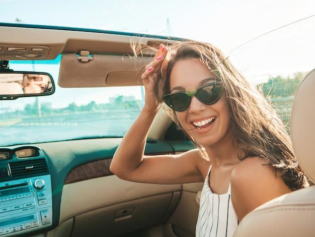 Retrato de uma jovem bonita e sorridente hipster feminina em um carro conversível