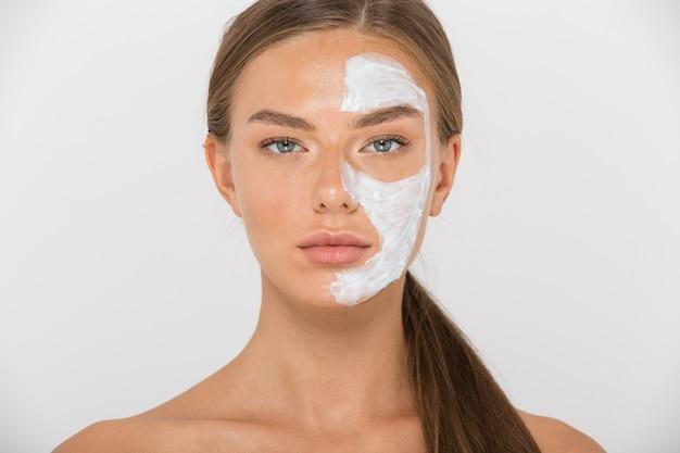Retrato de uma jovem bonita em topless isolada, olhando com metade do rosto coberto com máscara branca