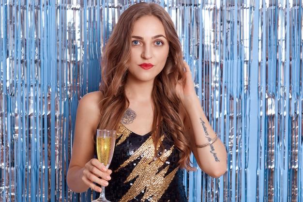 Retrato de uma jovem bonita em um lindo vestido preto coquetel, garota segurando uma taça com vinho ou champanhe nas mãos