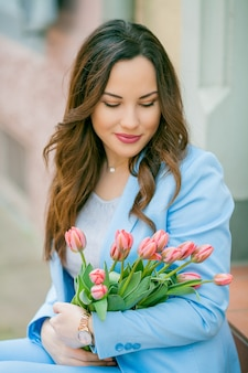Retrato de uma jovem bonita em um terno azul com um buquê de tulipas