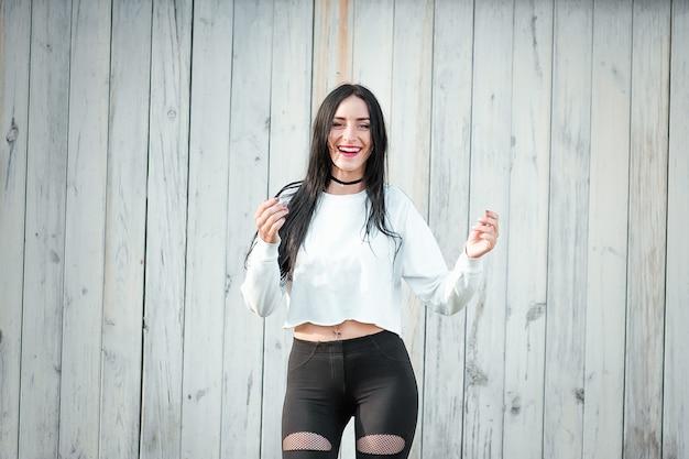 Retrato de uma jovem bonita em uma camiseta branca com cabelo preto. alegria e riso degeneram. emoções positivas. estilo de vida. beleza e juventude. em uma parede branca emoção positiva e alegre