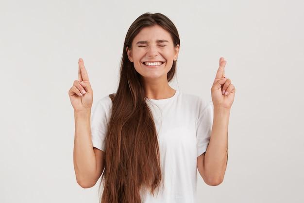 Retrato de uma jovem bonita feliz com cabelo comprido e olhos fechados usa uma camiseta com os dedos cruzados e faz um pedido isolado sobre a parede branca