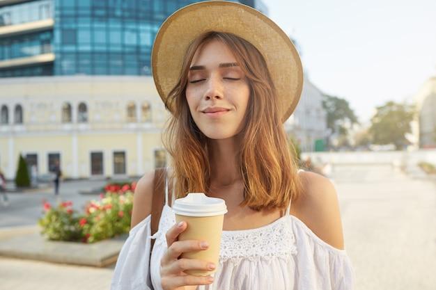 Retrato de uma jovem bonita feliz com os olhos fechados usa