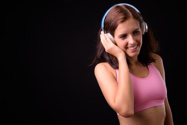 Retrato de uma jovem bonita feliz ouvindo música e pronto para a academia
