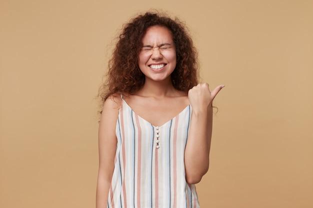 Retrato de uma jovem bonita morena cacheada franzindo a testa enquanto ri alegremente com os olhos fechados e mostrando de lado com o polegar, isolado no bege