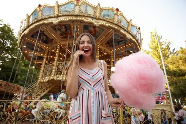 Retrato de uma jovem bonita morena de cabelos compridos com vestido de verão, olhando alegremente com um sorriso largo e sincero, em pé sobre o carrossel com algodão doce na mão