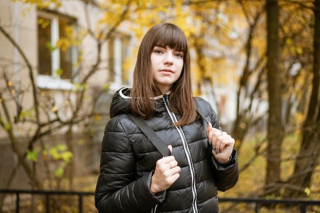 Retrato de uma jovem bonita no outono em um dia ensolarado.