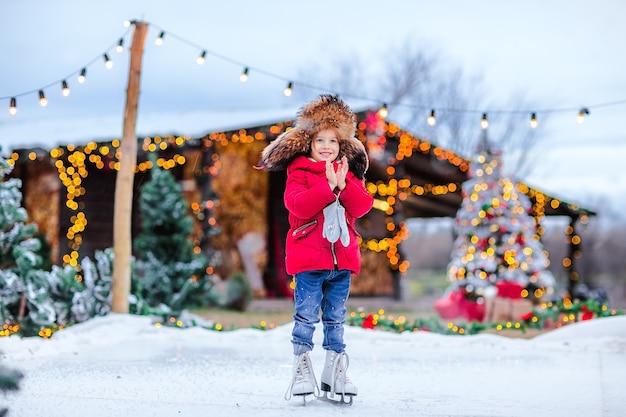 Retrato de uma jovem bonita no tradicional boné de pele russa com protetores de orelha e jaqueta vermelha de inverno e patins brancos, posando na pista de gelo contra o fundo de natal.