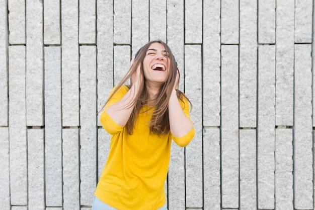 Retrato de uma jovem bonita, ouvindo música em fones de ouvido. ela está dançando, pulando e sorrindo. ela está vestindo roupas casuais. estilo de vida ao ar livre