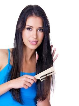 Retrato de uma jovem bonita penteando seus longos cabelos - isolado no branco