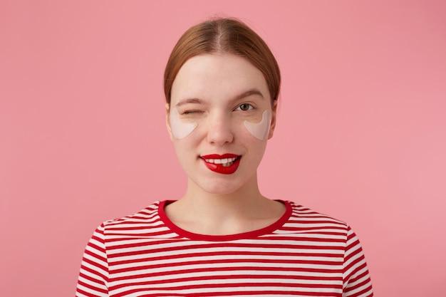 Retrato de uma jovem bonita piscando senhora ruiva com lábios vermelhos e com manchas sob os olhos, usa uma camiseta listrada vermelha, olha e morde os lábios, fica de pé.